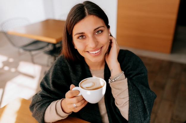 コーヒーカップを飲むカフェに座っている女性