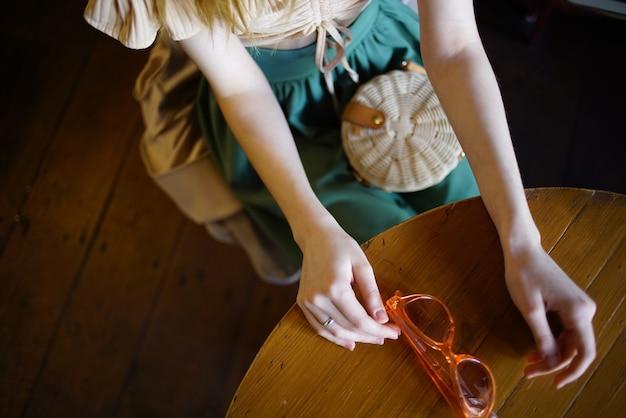 テーブルレストのカフェグラスに座っている女性