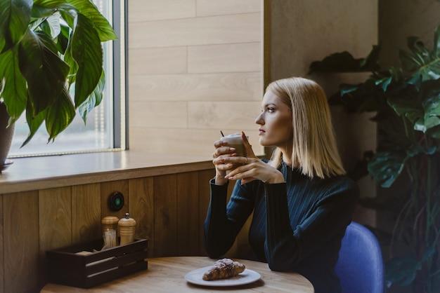 コーヒーとクロワッサンと朝のカフェに座っている女性