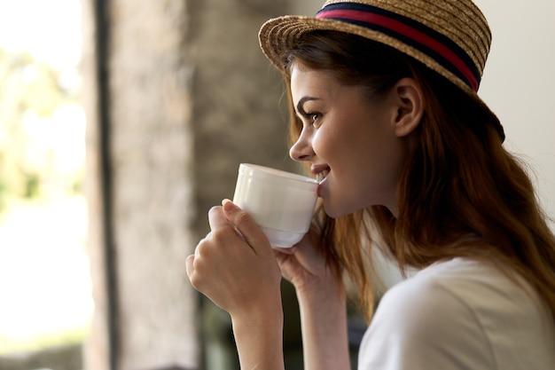Женщина, сидящая в кафе с чашкой напитка, расслабляющий завтрак