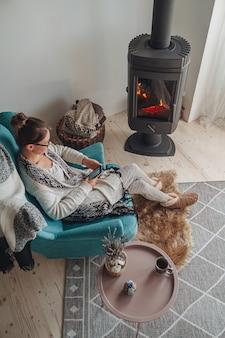Am을 사용하여 따뜻한 담요와 함께 아늑한 안락의자에 앉아 있는 여성