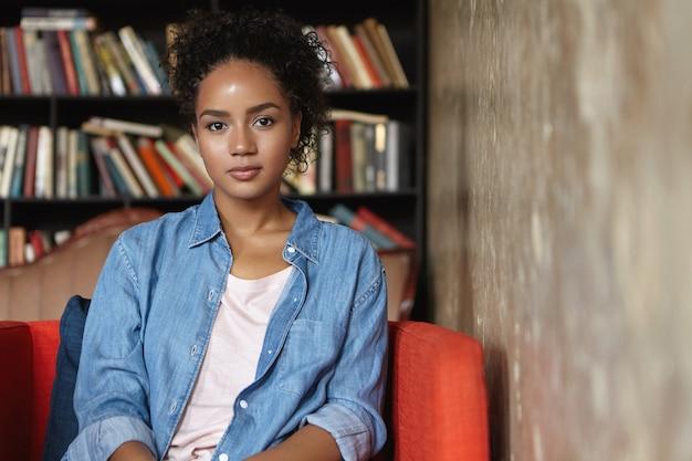 Женщина, сидящая в библиотеке на диване