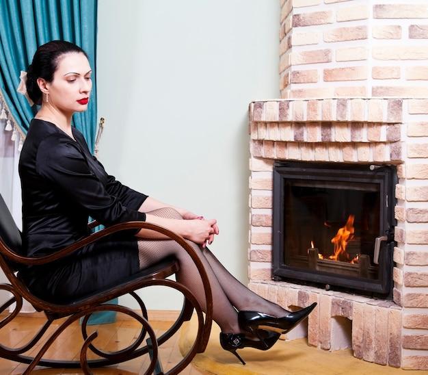 벽난로 앞 흔들 의자에 앉아있는 여자