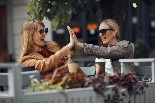 Женщина сидит в летнем городе и пьет кофе