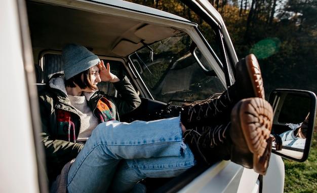 Женщина, сидящая в фургоне с вытянутыми ногами