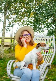 안락의자에 앉아 정원에서 휴대전화로 말하는 여자