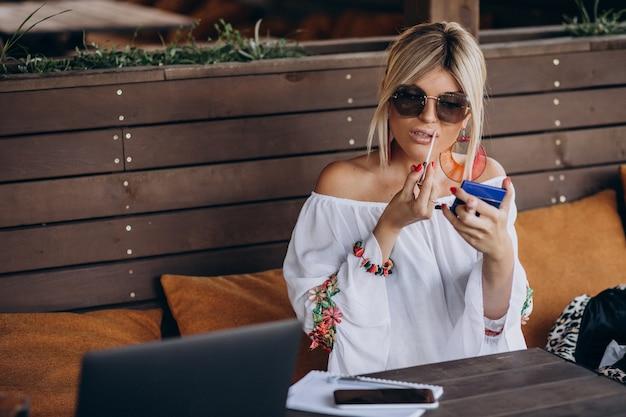 Женщина сидит в баре и использует помаду