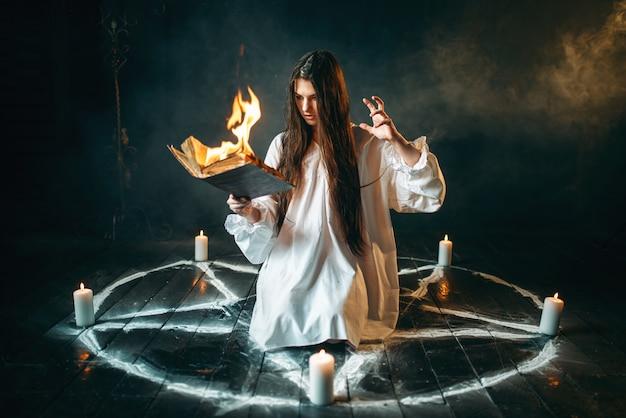 Женщина, сидящая в горящем круге пентаграммы, магия