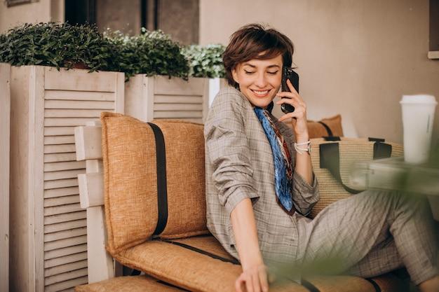 カフェに座って電話を使用している女性