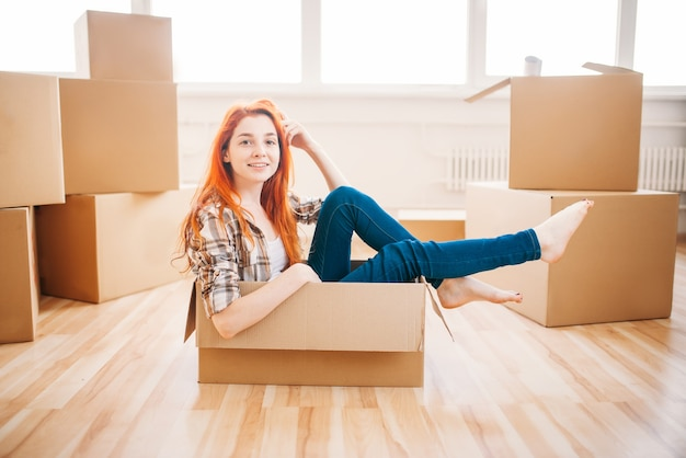 판지 상자에 앉아있는 여자, 집들이. 새 주택으로 이사