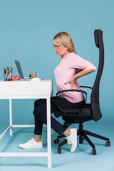 Женщина сидит в кресле страдает от боли в спине во время работы на ноутбуке