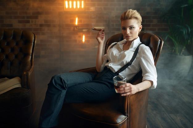 ウイスキーと葉巻が付いている椅子に座っている女性