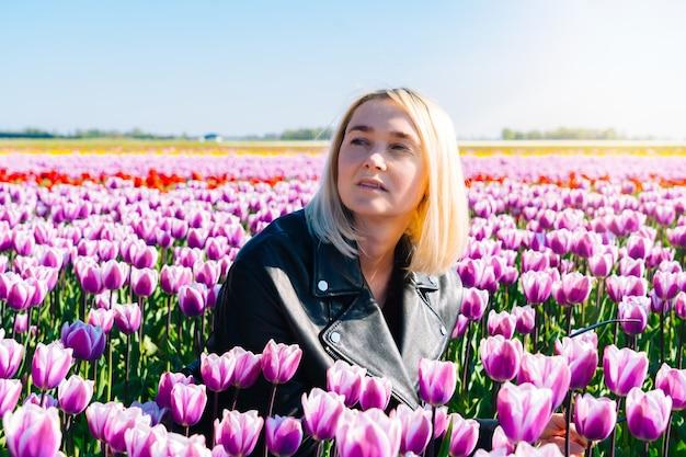 オランダ、アムステルダム地方の色とりどりのチューリップの花畑に座っている女性。オランダのチューリップ畑と魔法のオランダの風景。