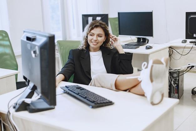 Женщина, сидящая в классе информатики. студентка сидит за компьютером. дама на перерыве.