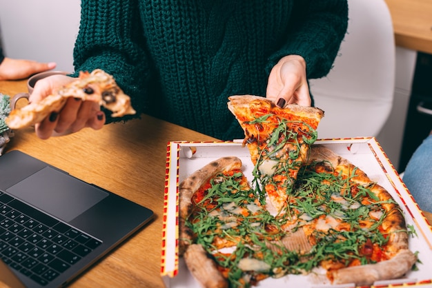 Женщина сидит перед ноутбуком в офисе и ест во время обеда с горячей вкусной пиццей