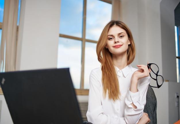 사무실 비서 작업 전문에서 노트북 앞에 앉아 여자