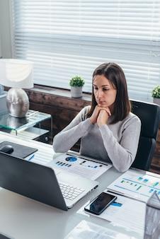 彼女の頭が彼女の手に寄りかかって机のノートパソコンの画面の前に座っている女性。