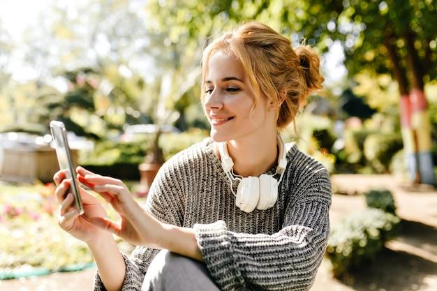 温室に座っている女性が自分の携帯電話で自分撮りをします