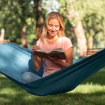 Женщина сидит в гамаке и читает