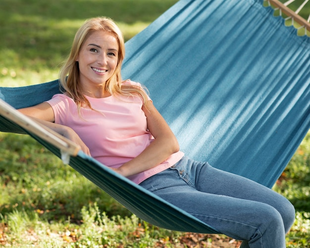 公園のハンモックに座っている女性