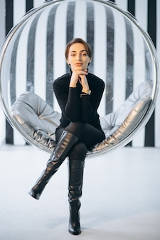 Woman sitting in hanging glass chair