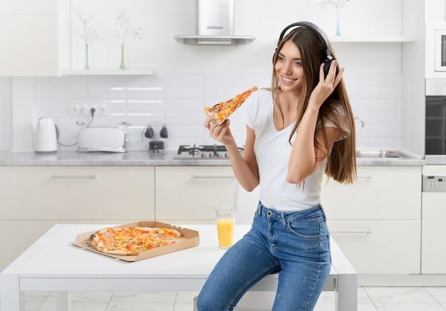 Женщина сидит в наушниках и ест вкусную пиццу