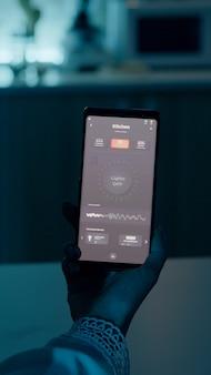 音声を使用してライトをオンにするスマートフォンを保持している自動化ライトシステムで家に座っている女性...