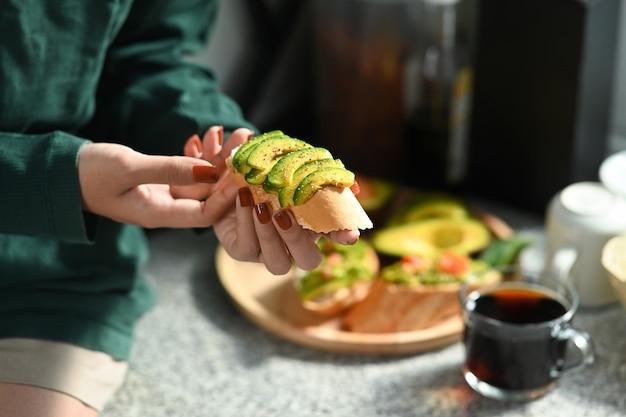 キッチンに座ってアボカドサンドイッチを食べる女性。