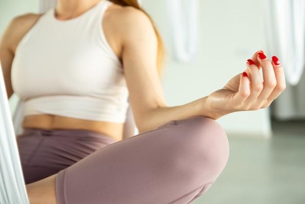 蓮華座に座っている女性は、禅のジェスチャーやムードラを行う手でハンモックでポーズをとる