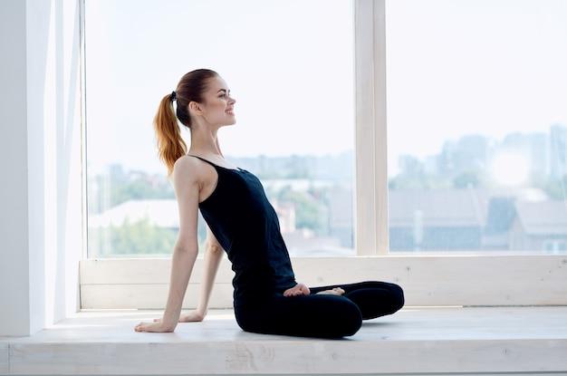 蓮華座に座っている女性が窓の近くで瞑想ヨガを行う
