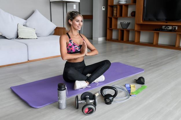 Женщина сидит в позе лотоса на коврике для йоги