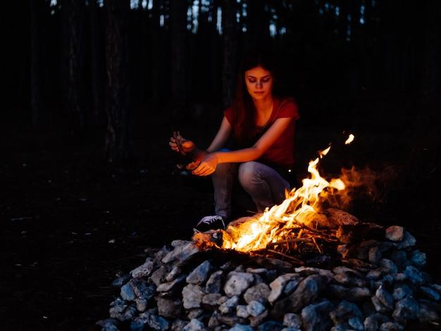 キャンプファイヤー休憩の森の近くの自然に座っている女性