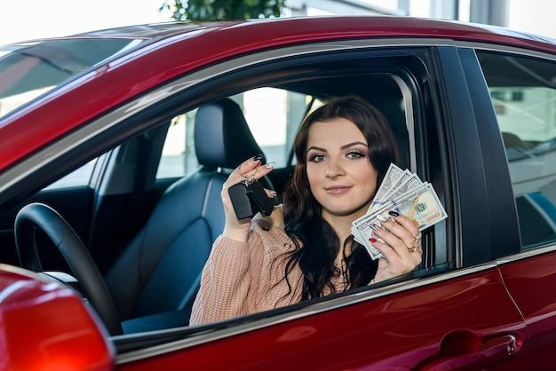 새 차에 앉아서 달러와 키를 보여주는 여자