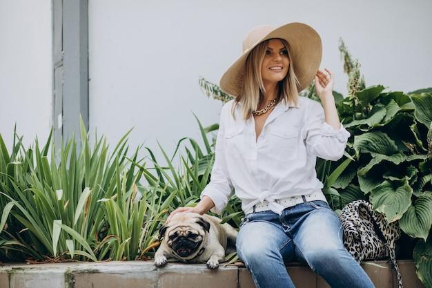 パグ犬のペットと一緒に公園に座っている女性