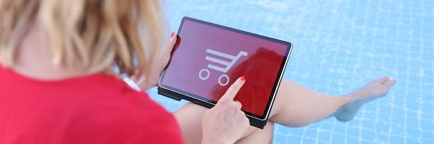 プールに座っている女性がタブレットでオンライン購入を行う