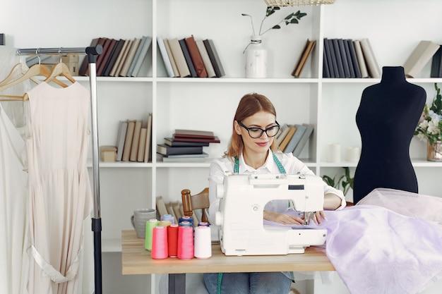 Женщина сидит в студии и шьет ткань