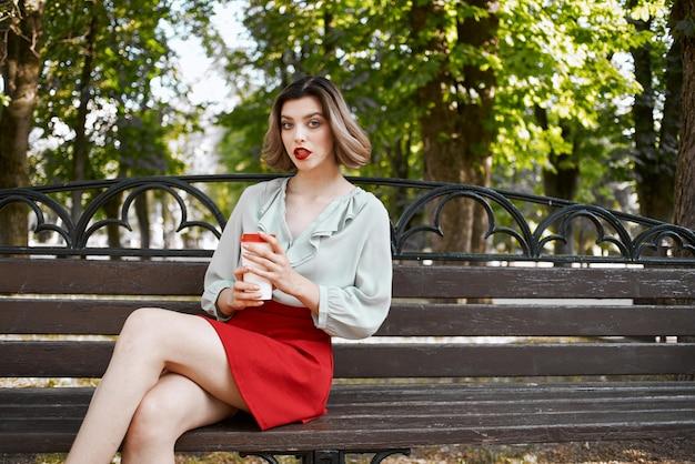 屋外でコーヒーを飲みながら夏の公園に座っている女性