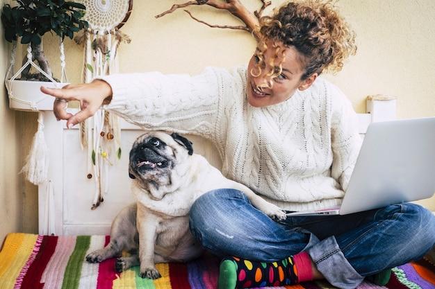Женщина сидит на балконе со своим другом мопсом обнимаются