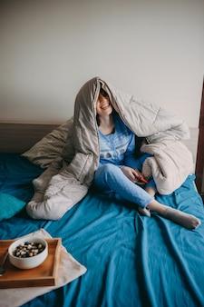 Женщина, сидящая в постели утром, накрытая одеялом, ест здоровые хлопья