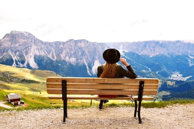 ドロミテの巨大な山々の景色を楽しみながらベンチの端に座っている女性
