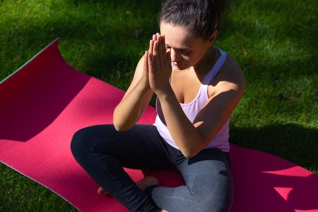 Женщина, сидящая в позе лотоса с закрытыми глазами, занимается йогой на коврике для йоги на зеленой траве в парке в теплый день Premium Фотографии