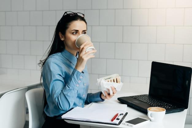 Женщина, сидящая в офисе за столом, пьет кофе