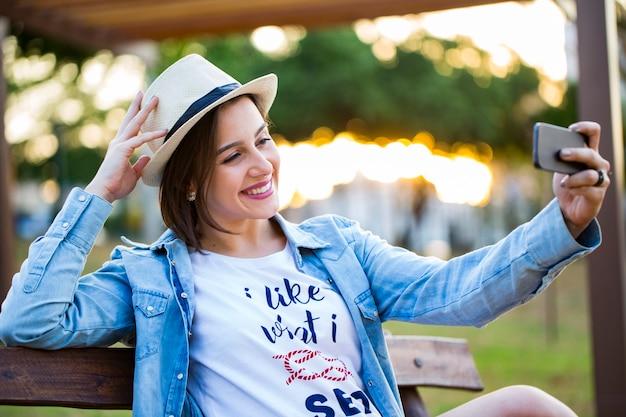 여자는 공원에 앉아 셀카, 행복하다