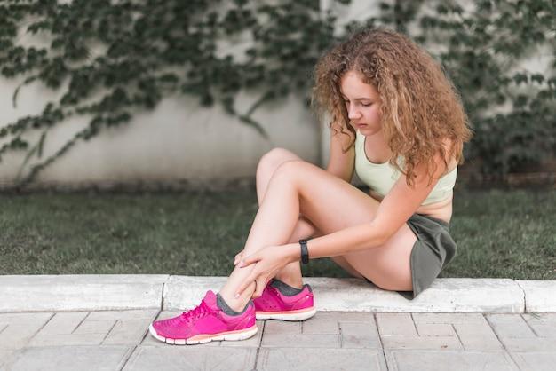 다친 된 발목을보고 공원에 앉아있는 여자