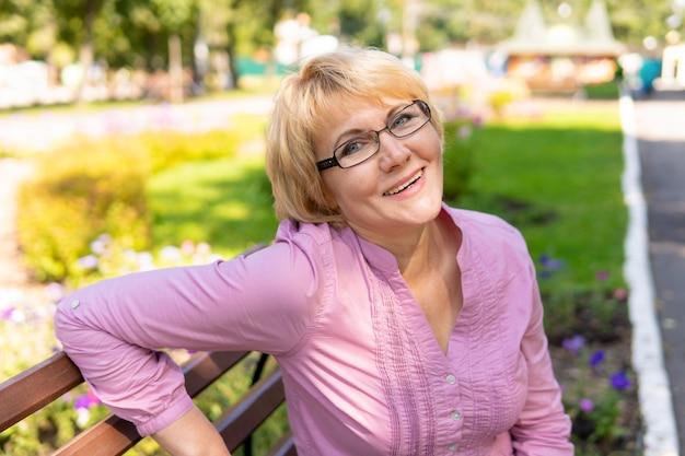 야외에 공원에 앉아 있는 여자. 안경을 쓴 중년 여성이 카메라 렌즈를 들여다보고 있습니다. 그녀는 미소를 지었다. 태양이 빛난다.