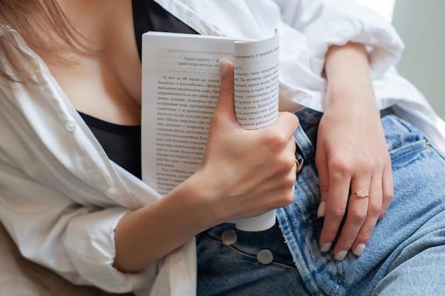 下着とボタンを外したシャツとジーンズでボタンを外したハエとボタンで本を読んで楽しんでいる部屋に座っている女性