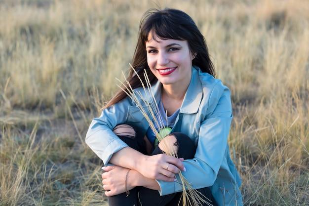 手に乾いた草を持って草原に座っている女性。