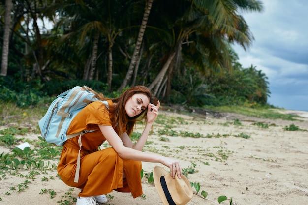 ヤシの木と熱帯のビーチに座っている女性