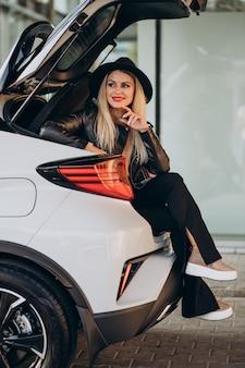 그녀의 차 트렁크에 앉아있는 여자