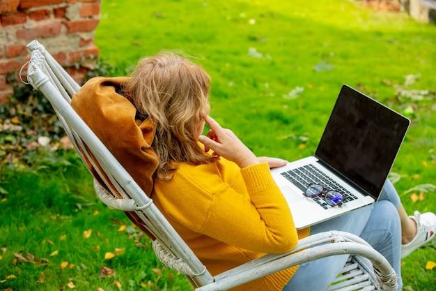 나무 안락의자에 앉아 정원에 있는 노트북에서 워킹하는 여자